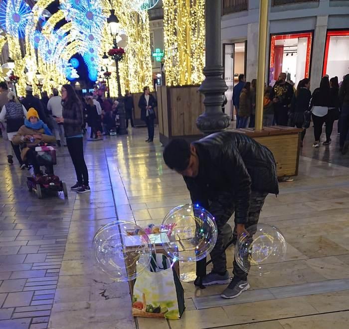 Man säljer ljusballonger på Calle Larios